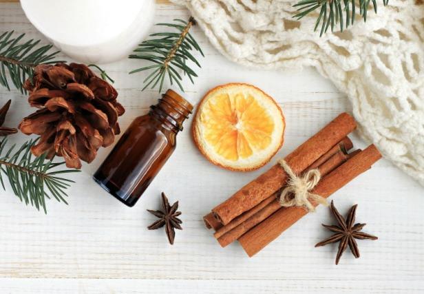 Winter home fragrances blend. Essential oils, orange, cinnamon sticks, anise, fir, cones, woolen blanket, top view.